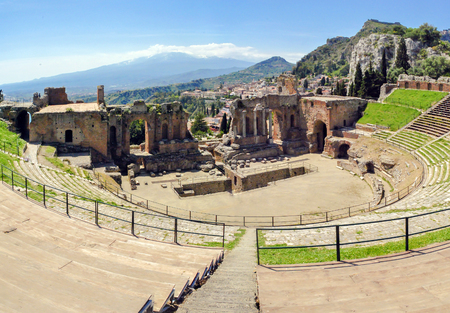 The famous and beautiful ancient greek theatre ruins Taormina with Etna volcano in the distance. outdoor shot, Sicily, Italy Stock Photo