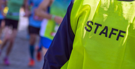 yellow bib staff service working during a marathon