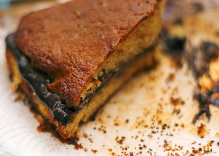 close up of leftover cake with chocolate cream and crumbs on a white  paper napkin Stock Photo
