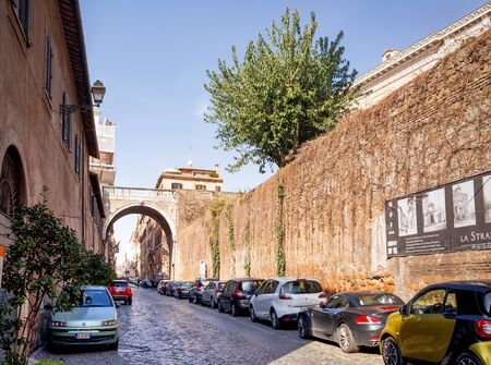 Rome, Italy, february 11, 2017: cars parked under an archway (Arco Farnese) along the ancient Via Giulia on a beautiful sunny day in Rome