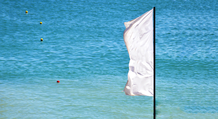a waving white flag with a blue sea and signaling buoys in the background Stock Photo