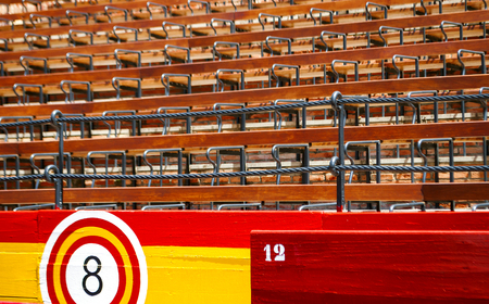 detail of the seats inside an ancient Spanish arena with wooden seats and barriers with the colors of the Spanish flag