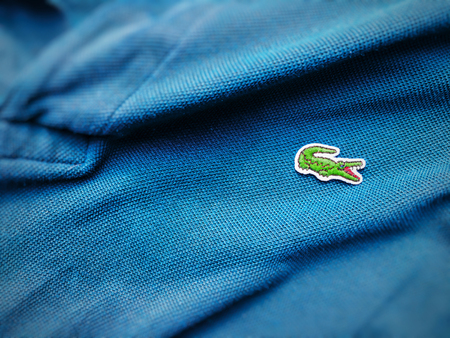 Rome, Italy, august 3rd 2018: close up view of a Lacoste blue shirt. Focus on the sewn crocodile Редакционное