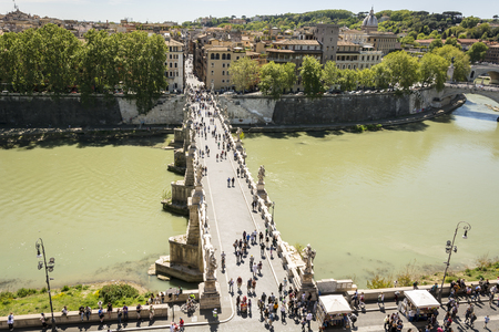Rome, Italy, April 17th 2017: people walking on the SantAngelo bridge along the River Tiber in Rome. The bridge was built by Emperor Hadrian in 134 to attach to the left bank of the river his mausoleum Editorial