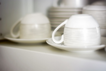 decorated coffee cups kept in a shelf of a white pantry. Interior shot Stock Photo