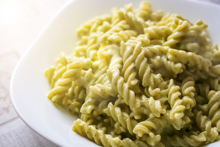 Closeup of a plate of fusilli pasta with green pesto sauce. Italian cuisine 免版税图像