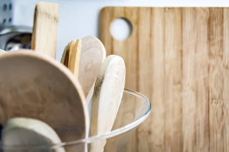 Wooden kitchen utensils in a glass container with a wooden cutting board in the background. Kitchen interior shot. Home decor and cooking concept