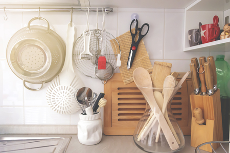 kitchen corner with various cooking utensils including a colander, knives and wooden utensils in a glass container