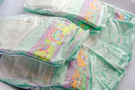 Group of disposable diapers arranged over a white changing table. Hygiene and health care for baby