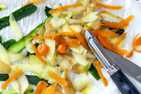 Vegetable peels of carrots, potatoes and zucchini freshly peeled with a peeler. Concept of food and healthy lifestyle. Stock Photo