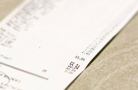 Nahaufnahme der Gesamtmenge der Lebensmitteleinkäufe im Supermarkt, die auf einem Papierbeleg gedruckt sind. Einkaufsliste für Lebensmittel