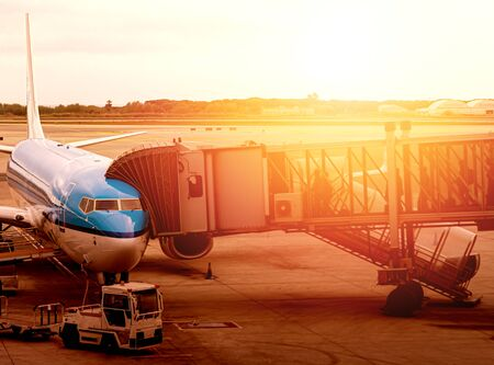 jet bridge attached to the fuselage of a commercial aircraft to allow travelers to board. Passenger boarding operations at an international airport during a sunset