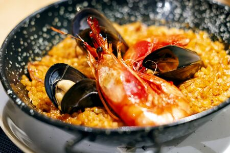 Paella with mariscos in a black pan, a typical dish of traditional Spanish cuisine based on seafood and rice. Traditional cuisine