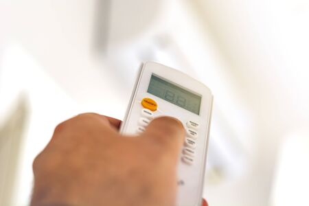 close-up view of a hand adjusting the air conditioning temperature using the remote control. Home comfort. Air conditioning and appliances Banque d'images