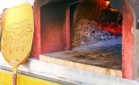 wood oven for baking pizza with ashes, burning embers and fire. Leaning against the oven there is a yellow shovel to take the pizza from the oven once it is ready