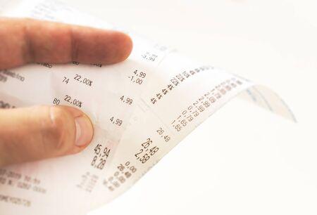 menschliche Finger, die eine Papierquittung mit der Gebührenrechnung halten und den Gesamtbetrag überprüfen. Inländische Finanzierung. Steuerquittung auf einer Rolle Thermopapier Standard-Bild