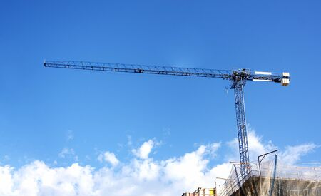 a crane lifting weights on a construction site with a blue sky and clouds on the background. construction and construction engineering.