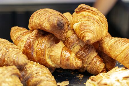 a group of croissants stacked on a tray. Baked product.