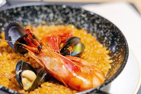 Valencian paella with rice, saffron and seafood served in a special pan. Typical recipe of Spanish cuisine.