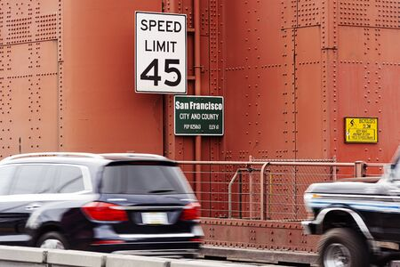 Traffic signs about speed limits and information panels on a tower of the Golden Gate Bridge in San Francisco. Entrance and information on the population of San Francisco