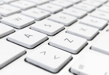 Close-up detail of a computer keyboard with white keys and a gray background. Letters and symbols on the keys. Technology and communication via the internet