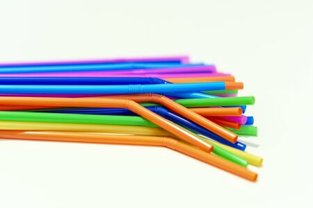 group of plastic straws of various colors on a white background. Global warming and plastic pollution. Environmental issues. Party and refreshment.