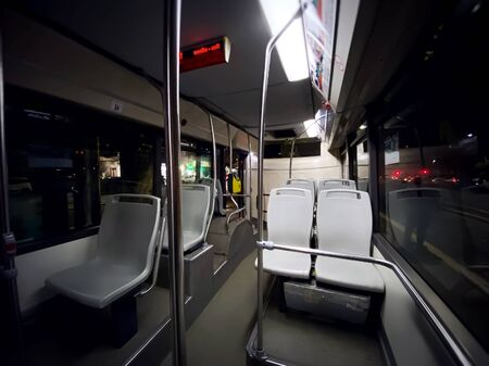 interior of a public transport bus with empty gray seats and no passengers. Transport and urban mobility. Wide angle shot