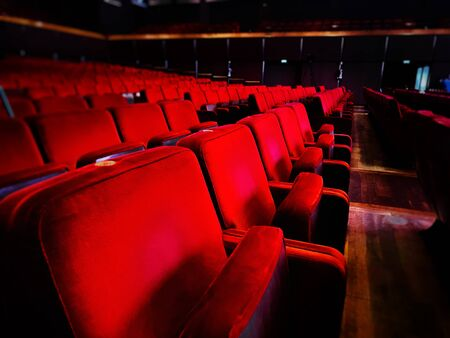a row of empty red velvet armchairs inside an auditorium. Interior of a theater or cinema