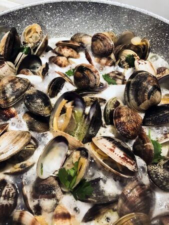 cooking clams in a stone pan using parsley and white wine. Cuisine and restaurant recipes. Shell seafood