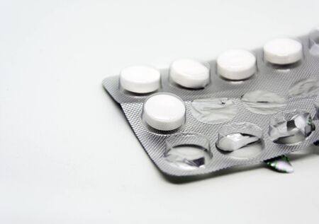 white pills packed in an aluminum and plastic blister with some missing pills already used. Pharmaceutical products for the treatment of diseases. medicine and chemistry Stock fotó