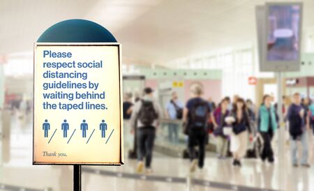 a sign inside an airport warns of the need to maintain the minimum safety distance between people to avoid contagion during the COVID-19 Coronavirus pandemic. Airport security measures.