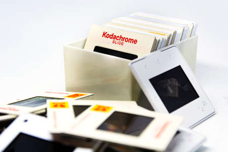 Rome, Italy, 22 April 2020: a group of Kodachrome brand slides from the 70s inside a plastic box isolated on a white background. Photographic supports now obsolete.