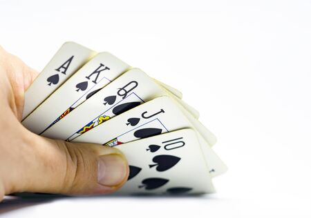 a gambler reveals a royal flush in spades. Gambling and luck. Decisions and risks. Isolated on a white background