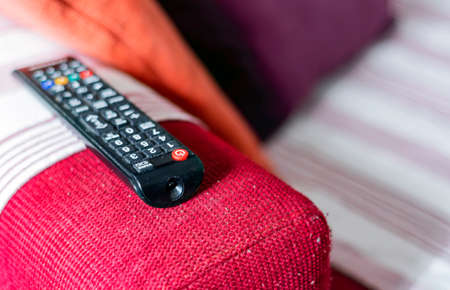 the dusty television remote control on the armrest of a red fabric sofa. Lint on the sofa. Sedentary life and home entertainment. Selective focus on the remote control Standard-Bild