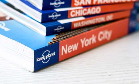 Rome, Italy, November 15th 2020: The Lonely Planet logo on the back of a series of stacked travel guide books. Famous Australian brand of tour guides. Illustrative editorial Editorial