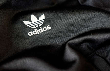 Rome, Italy, November 15th 2020: the Adidas logo sewn on a black recycled polyester fabric. Sportswear and iconic logo. Famous German sportswear brand. Illustrative editorial Editorial