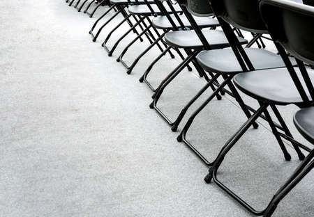 a group of empty folding chairs arranged in a row in a conference room. Copy space. Gray background