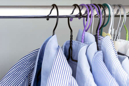 Group of light blue striped shirts hanging on the rod of a white wardrobe. Men's fashion and classic clothing. Standard-Bild