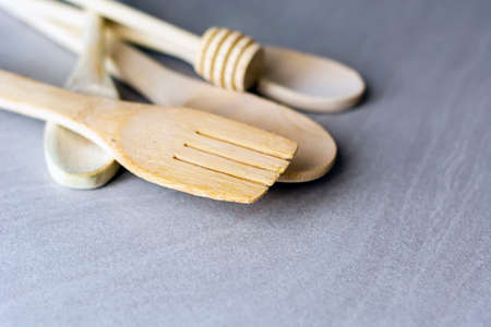 Group of wooden kitchen utensils arranged on a gray marble table. Selective focus on the carving fork.