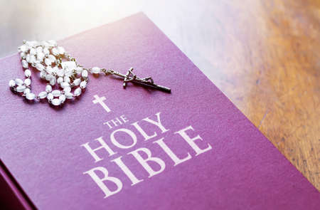 A rosary of white beads with a silver crucifix above the cover of the closed holy bible book. Religion and hope. Religious objects for praying