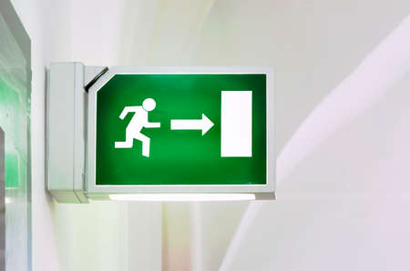 Illuminated green emergency exit sign. Stylized human figure running towards a door. Security and infographics Standard-Bild