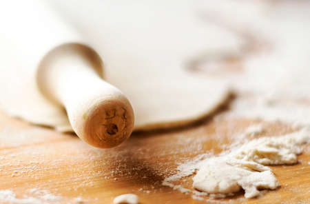 Wooden rolling pin on a wooden surface with some flour and a dough. Preparation of baked food