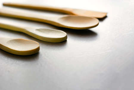 Group of wooden kitchen spoons arranged on a gray marble table. Kitchen utensils and cooking. Wooden material