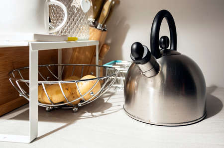 Modern steel kettle next to a basket of potatoes in a poorly lit domestic kitchen. Home life and kitchen accessories Stock Photo