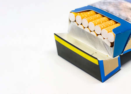 Group of cigarettes inside an open blue packet isolated on a white background. Unhealthy addictions. Cancer prevention