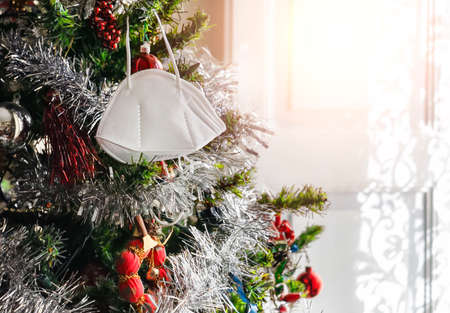 Christmas tree decorated with a protective surgical mask. Christmas 2020 with the danger of the Covid-19 coronavirus pandemic. Personal safety and precaution. Virus prevention