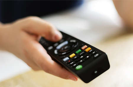 Caucasian woman hands holding television remote control. Selective focus. Infrared wireless technology. Relaxing while watching television choosing the channels to watch