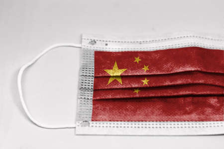 The national flag of China printed on a disposable surgical mask.   Health and medicine