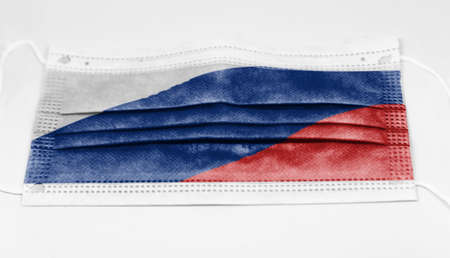 The national flag of Russia printed on a disposable surgical mask. Coronavirus covid-19 pandemic prevention and protection. Health and medicine