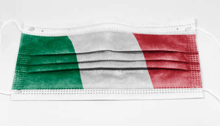 The national flag of Italy printed on a disposable surgical mask. Coronavirus covid-19 pandemic prevention and protection. Health and medicine Stock Photo
